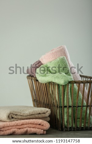 Basket with clean towels on table against light background #1193147758