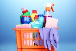 Basket with cleaning items on blue background