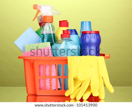Basket with cleaning items on green background - stock photo