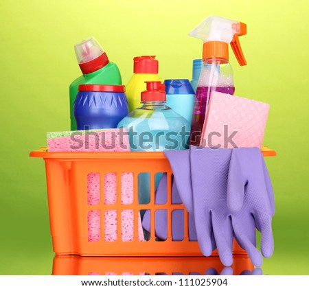 Basket with cleaning items on green background