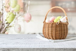 Basket with colorful pastel eggs on kitchen wooden tabletop. Spring easter composition. Space for text or design.