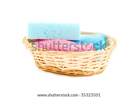 basket with colorfull towels and sponge isolated on white