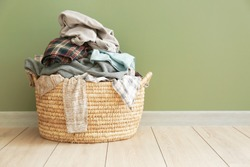 Basket with dirty laundry on floor