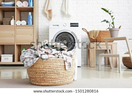 Basket with dirty laundry on floor in bathroom