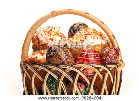 Basket with Easter cakes and painted eggs over white background
