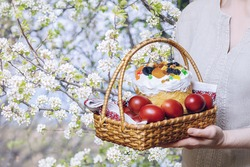 Basket with Easter eggs in hands on a background of blooming cherries.