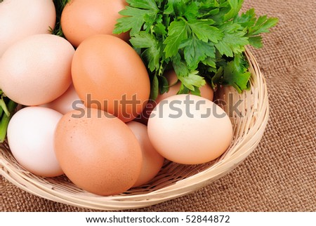 Basket with eggs on sackcloth with greens