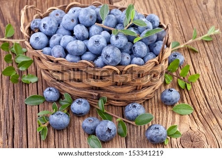 basket with fresh blueberry on wooden background