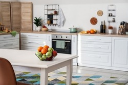 Basket with fresh fruits on dining table in kitchen