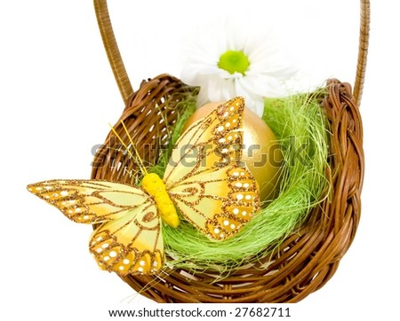 Basket with golden easter egg,butterfly and spring flower isolated on white background.Clipping path included.