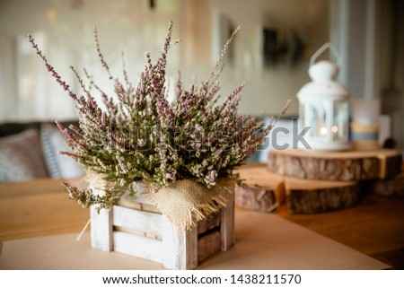 Basket with Heather on the table.heather in a basket . Autumn decorations.pink and purple flowers heather,heath in wooden box,autumn plants and lantern.country house. Seasonal decorations #1438211570