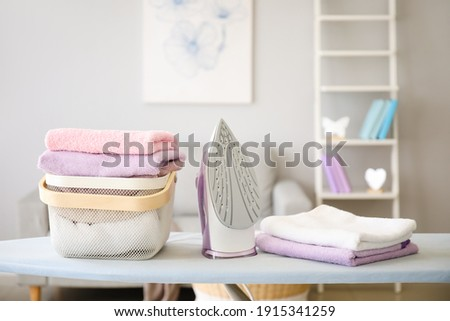 Basket with laundry and iron on board Photo stock ©