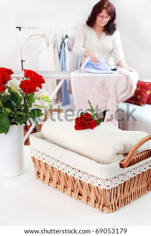 Basket with laundry and ironing board with housewife in background