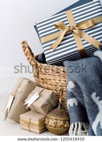Basket with plaid and different present boxes decorated for Christmas.