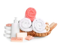 Basket with soft towels and toiletries on white background