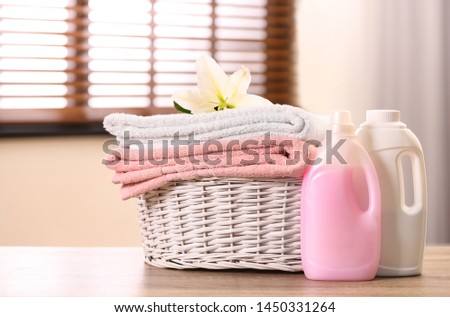 Basket with towels and detergents on table in room Foto stock ©