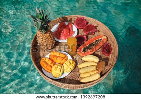 Basket with tropical fruits ( pineapple, banana, papaya, pitahaya, manho juice) floating in the pool. Cocept healthy food, floating breakfast tray in the swimming pool. Summer vacation on Bali Foto stock ©