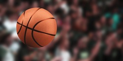 Basketball ball on a blurred background of a crowd of people. Sport competitions.