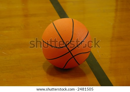 basketball ball on a court - wooden floor with the reflection of the ball on the wood - stock photo