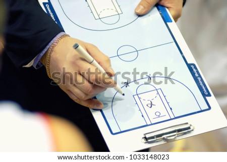 Basketball coach write tactics on coaching board