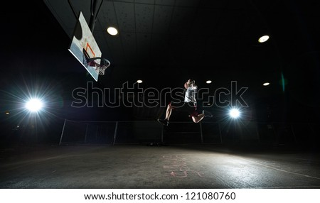 Basketball court at night with lights on, basketball player jumping and aiming at hoop