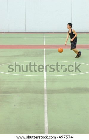 basketball court in muted tones. player with slight motion blur - stock photo
