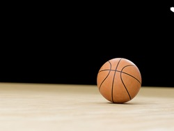 Basketball court wooden floor with ball isolated on black with copy-space