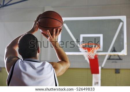 basketball game playeer shooting on basket indoor in gym