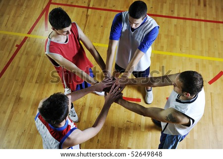 basketball game players holding together as team representing team spirit