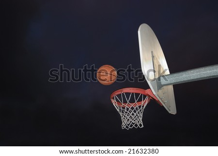 Basketball going into the hoop at an outdoor court in the dark