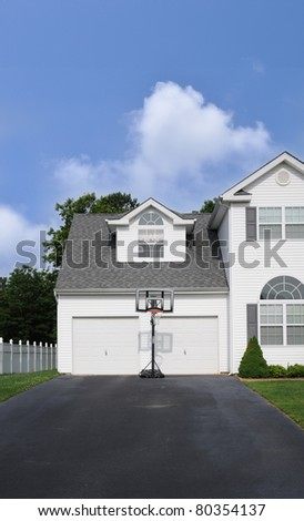 Basketball Hoop in front of Double Garage Doors on empty Suburban Residential Home Driveway