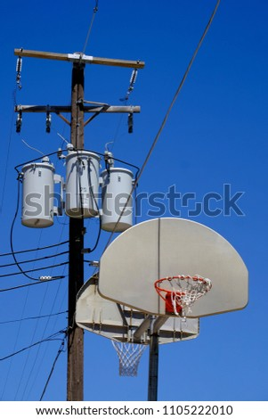 Basketball hoop innercity inner city with powerlines power lines above blue sky #1105222010