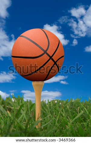 Basketball on golf tee from the ground level with grass and cloudy sky