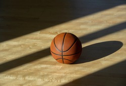 Basketball on hardwood court floor with natural lighting. Workout online concept