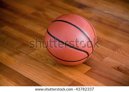 Basketball on the hardwood basketball floor in a stadium