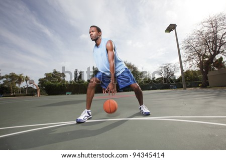 Basketball player dribbling the ball between his legs