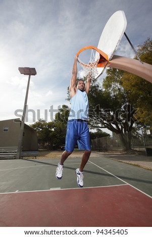 Basketball player hanging from the hoop - stock photo
