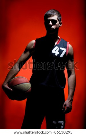 Basketball player holding ball isolated on red background