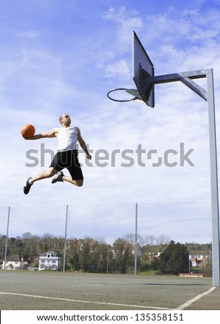 Basketball Player in mid air about to Slam Dunk