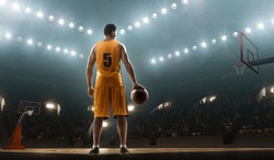 Basketball player in sports uniform with a ball on a floodlit professional basketball court. View from the back