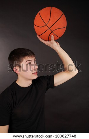 Basketball player ready to throw the ball isolated on a black background