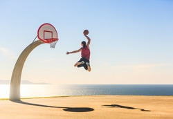 Basketball Player scoring an amazing slam dunk outdoors.