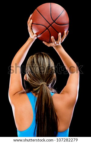 Basketball player shooting the ball - isolated over a black background