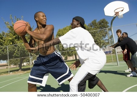 Basketball player trying to guard another as he passes ball
