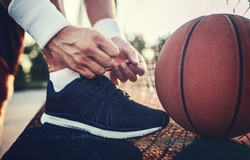 Basketball player tying sport shoes. Sport, recreation concept