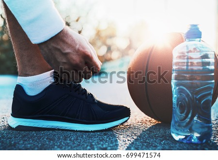 Basketball player tying sport shoes. Sport, recreation concept #699471574