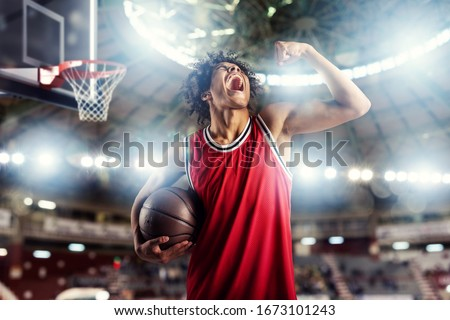 Basketball player wins the match at the basket stadium full of spectators.