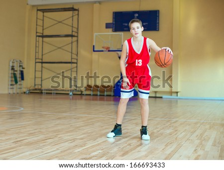 Basketball player with a ball in his hands and a red uniform.  Basketball player practicing in the gym #166693433