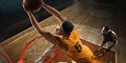 Basketball players fight for a ball near the hoop in a sports gym. High-angle shot.