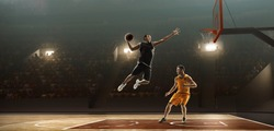 Basketball players fight for the ball on professional arena